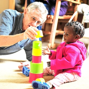 African impact volunteer with child