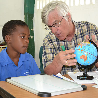 Volunteer from Global Volunteers teaching geography to a student