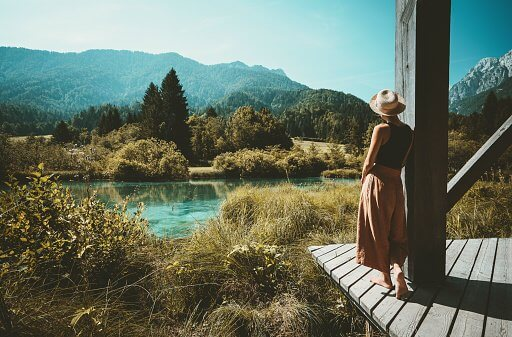 photo of a woman looking over a beautiful blue lake, with mountains in the distance